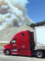 A truck drives past a heavy plume of smoke from a wildfire next to the Interstate 5 freeway in Santa Clarita, Calif., Wednesday, June 24, 2015. Hundreds of firefighters are trying to protect homes from the wildfire ripping through brushy canyonlands north of Los Angeles. The fire began in the Newhall area of Santa Clarita on the shoulder of Interstate 5.  (Christopher Brown via AP)