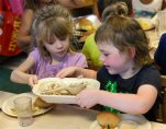 Rebekah Webb, left, shares a family-style meal with Zoe Turner during lunch with other five-year-olds at the Olathe Family YMCA in Olathe, Kan., Wednesday, June 24, 2015. As early childhood teachers lament toddlers too large to fit in playground swings, officials are mulling changes designed to make meals served to millions of kids in day care healthier.  (AP Photo/Orlin Wagner)