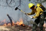 FILE - In this June 13, 2013 file photo, a volunteer firefighter helps contain a spot fire in an evacuated area of forest, ranches and residences, in the Black Forest wildfire area, north of Colorado Springs, Colo. The leaders of the Interior and Agriculture departments discussed the nationwide outlook for the 2015 wildfire season in a conference call from Denver on Tuesday, June 8, 2015. Interior Secretary Sally Jewell and Agriculture Secretary Tom Vilsack reviewed the risk of catastrophic wildfires, especially in the West. (AP Photo/Brennan Linsley, file)