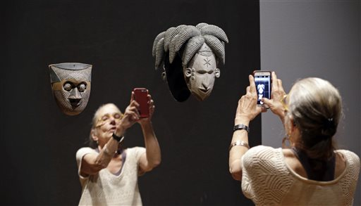 "Kara Jakobs tries to take a photo of herself with a mask mounted on a mirror as part of the the show ""Disguise: Masks & Global African Art"" at the Seattle Art Museum on Sunday, June 28, 2015, in Seattle. Race, identity and the masks people wear are the themes explored in the new exhibit of contemporary, multimedia art, which showcases masks from the museum's collection alongside contemporary art, much of it created just for this show by African artists and those of African descent. The show will be traveling to Los Angeles and New York after Seattle. (AP Photo/Elaine Thompson)"