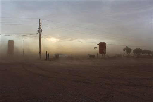 In this Saturday, June 27, 2015 photo provided by Melissa Edwards, a dust storm blows through Vertuccio Farms in Mesa, Ariz. The first big dust storm of the monsoon season slammed the Phoenix area on Saturday with winds snapping utility poles and leaving thousands without power. (Melissa Edwards via AP)