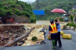 In this Thursday, June 18, 2015 photo, government officials look at a road that collapsed due to flooding in Kaili city in southwestern China's Guizhou province. Heavy storms that swept through several southern Chinese provinces this past week have killed 18 people and left four more missing, according to the Ministry of Civil Affairs. (Chinatopix Via AP) CHINA OUT