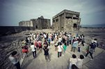 "In this June 29, 2015 photo, tourists visit a part of Hashima Island, commonly known as Gunkanjima, which means ""Battleship Island,"" off Nagasaki, Nagasaki Prefecture, southern Japan.  The island is one of 23 old industrial facilities seeking UNESCO's recognition as world heritage ""Sites of Japan's Meiji Industrial Revolution"" meant to illustrate Japan's rapid transformation from a feudal farming society into an industrial power at the end of the 19th century. UNESCO's World Heritage Committee is expected to approve the proposal during a meeting being held in Bonn, Germany, through July 9. (AP Photo/Eugene Hoshiko)"