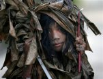 A muddied girl, donning a cape made of dried banana leaves, makes the rounds of the streets to collect candles prior to attending a mass to celebrate the Feast Day of St. John the Baptist in the village of Bibiclat, Aliaga township, Nueva Ecija province in northern Philippines,Wednesday, June 24, 2015.  At dawn every June 24th, people from Bibiclat village in the northern Philippines' Nueva Ecija province pay homage to their patron saint, John the Baptist, by gathering in silence in a swampy field to cover themselves in mud, donning mud-drenched capes made of dried banana leaves. (AP Photo/Bullit Marquez)
