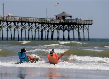Vacationers sit in chairs in the surf in Oak Island, N.C., Monday, June 15, 2015. A 12-year-old girl from Asheboro lost part of her arm and suffered a leg injury, and a 16-year-old boy from Colorado lost his left arm about an hour later and 2 miles away in two separate shark attacks late Sunday afternoon. (AP Photo/Chuck Burton)