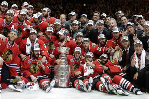 Members of the Chicago Blackhawks pose for pictures as they celebrate after defeating the Tampa Bay Lightning in Game 6 of the NHL hockey Stanley Cup Final series on Monday, June 15, 2015, in Chicago. The Blackhawks defeated the Lightning 2-0 to win the series 4-2. (AP Photo/Nam Y. Huh)