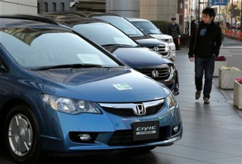 FILE - In this Jan. 30, 2010 file photo, a man looks at Honda Motor Co.'s Civic hybrid cars in front of the Japanese automaker's headquarters in Tokyo. Slow sales and falling gasoline prices have prompted Honda to stop selling gas-electric hybrid and natural gas-powered versions of its Civic compact car, the automaker said Monday, June 15, 2015. (AP Photo/Koji Sasahara, File)