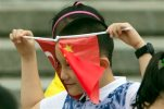 A child plays with Chinese and Turkish national flags before a welcome ceremony for Turkey's President Recep Tayyip Erdogan at the Great Hall of the People in Beijing, Wednesday, July 29, 2015. (AP Photo/Ng Han Guan)