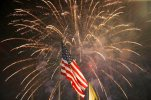 """FILE - In this July 4, 2015 file photo, fireworks explode behind a United States flag during a Fourth of July celebration at State Fair Meadowlands in East Rutherford, N.J. A video posted on an Al Jazeera YouTube channel over the Fourth of July weekend mocks Americans for dubious """"achievements"""" in obesity, pornography production and gun ownership. The satirical item, under two minutes long, was produced out of San Francisco by a digital arm of the Qatar-based Al Jazeera news network.  (AP Photo/Julio Cortez, File)"""