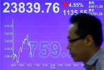 A man walks past  a screen showing the Hong Kong share index at a brokerage firm in Hong Kong, Wednesday, July 8, 2015. The Hang Seng Index has dropped in morning trading following more big losses on mainland markets. Chinese stocks led a slump in Asian markets on Wednesday as the sell-off in Shanghai intensified and Greece's future in the euro remained highly uncertain. (AP Photo/Kin Cheung)