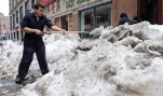 FILE - In this March 4, 2015 file photo, waiter Melvin Angel shovels snow outside the restaurant he works at in the Chinatown neighborhood of Boston. The U.S. economy's stumble at the start of 2015 is dragging down the world's growth to the lowest level since the Great Recession, the International Monetary Fund said Thursday, July 9, 2015.  The American economy, the world's biggest, shrank at a 0.2 percent annual rate from January to March, hurt by nasty weather.  (AP Photo/Charles Krupa, File)