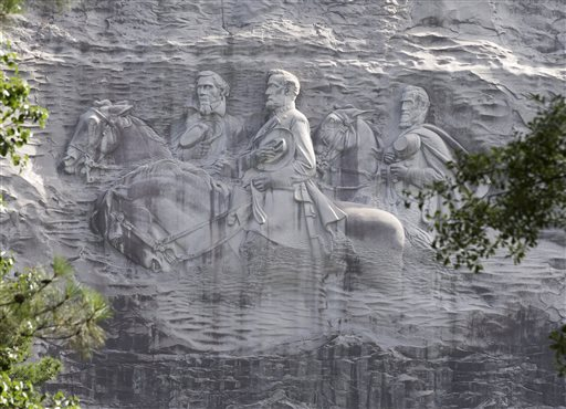 """FILE - A Tuesday, June 23, 2015 file photo shows a carving depicting confederates Stonewall Jackson, Robert E. Lee and Jefferson Davis, in Stone Mountain, Ga. The """"Confederate Memorial Carving"""" in a state park outside of Atlanta is once again stirring controversy, as Georgia officials try to decide what, if anything, to do about a huge sculpture that memorializes three of the South's Civil War heroes but causes offense to blacks and others.  (AP Photo/John Bazemore, File)"""