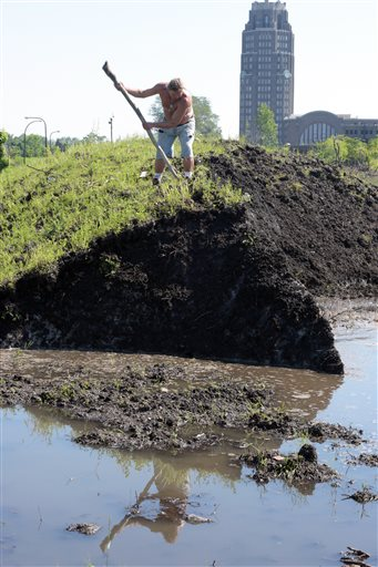 "Robert A. Raczka uses a stick on top of this dirt-covered snow ""glacier"" that still hasn't melted at the Central Terminal on Buffalo's East side eight months ago, Tuesday, July 28, 2015. City crews dumped snow in the lots after a lake-effect storm dumped more than 7 feet on parts of Buffalo and the surrounding area the week before Thanksgiving. Eight months later, some of it is still there. (AP Photo/Gary Wiepert)"