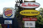 FILE - This Aug. 25, 2014, file photo, shows signs for Burger King and Tim Hortons locations in Ottawa, Ontario. The parent company of Burger King and Tim Hortons, reported Monday, July 27, 2015, a better-than-expected quarterly profit after global sales climbed at established locations for both fast-food chains. (Sean Kilpatrick/The Canadian Press via AP, File)