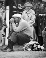 FILE - In this July 5, 1960 file photo, Arnold Palmer, U.S. Open Champion, sits on his golf bag and relaxes halfway through his troublesome second round of qualifying play in the British Open Championship at St. Andrews, Scotland. At that point, the 10th tee, Palmer had 36. On the second nine holes he shot a 39 for an over par 75 in a heavy downpour in first qualifying match. (AP Photo)