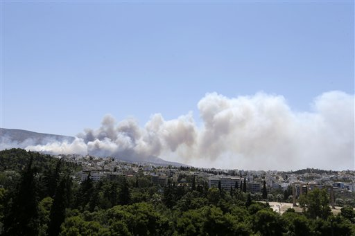 Smoke from a forest fire travels over the eastern suburbs of Athens on Friday, July 17, 2015. Another fire in Peloponnese, in southern Greece, is burning out of control. The forest fire is being battled by firefighters assisted by water-dropping planes and helicopters, authorities evacuating three villages and the coast guard rescuing scores of people trapped on a beach. (AP Photo/Thanassis Stavrakis)