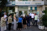 People stand in a queue to use an ATM outside a closed bank, next to a sign on the plant, bottom right, reading ''NO'' in Athens, Tuesday, June 30, 2015. It's crunch time for Greece, with the European part of its international bailout expiring Tuesday and with it any possible access to the remaining rescue loans it contains that it needs to pay its debts. As a result, the government is unlikely to repay a roughly 1.6 billion-euro ($1.87 billion) debt to the International Monetary Fund due Tuesday, too — a move that increases fears the country is heading to a messy default and potential exit from the euro currency. (AP Photo/Thanassis Stavrakis)
