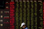A man walks past an electric board displaying stock prices at a brokerage house in Beijing, China, Wednesday, July 8, 2015. China's central bank has promised more credit to finance stock trading in the latest move aimed at stopping a plunge in stock prices that has prompted hundreds of companies to suspend trading in their shares. (AP Photo/Andy Wong)