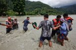 Nepalese rescue team helps local people cross a river after a foot bridge was destroyed by floods in Thulakhet, about 200 kilometers (125 miles) west of Kathmandu, Nepal, Friday, July 31, 2015. Landslides caused by heavy rains buried several mountain villages in Nepal on Thursday as bad weather hampers the search for others, authorities said. (AP Photo/Niranjan Shrestha)