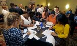 In this photo taken, Wednesday, July 15, 2015, job seekers attend a job fair in Miami Lakes, Fla. The Labor Department reports on the number of people who applied for unemployment benefits for the week ending July 11 on Thursday, July 16, 2015. (AP Photo/Alan Diaz)