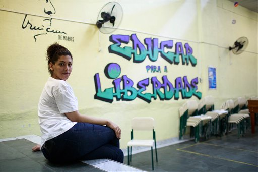 "In this July 8, 2015 photo, trangender inmate Estefanie Ferraz poses for a portrait next to a mural that reads in Portuguese: ""Educate for freedom"" as she serves time at the Evaristo de Moraes prison in Rio de Janeiro, Brazil. Usually a highlight of life for prisoners held in overcrowded cells, sunbaths were a nightmare for Ferraz. After shaving off her hair, guards at one all-male facility forced her to remove her shirt in the courtyard, exposing her implanted breasts to hundreds of fellow prisoners. ""It was beyond horrible,"" said Ferraz, ""Everyone was staring, cat-calling, screaming at me."" (AP Photo/Mauro Pimentel)"