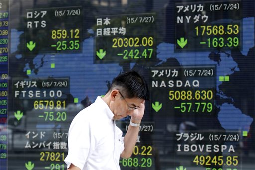 A man walks past an electronic stock board of a securities firm in Tokyo, Monday, July 27, 2015. The Shanghai share index dived more than 8 percent Monday as Chinese stocks suffered a renewed sell-off despite government efforts to support the market.  Other Asian markets also were lower.  (AP Photo/Ken Aragaki)