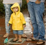 Ezekiel Ekinaka, 1, with his parents Aaron and Juliet, wears a raincoat as he experiences rain for the second time in his life, at the San Clemente, Calif. Ocean Festival before the public was urged to evacuate due to lightning on Saturday, July 18, 2015. (Mindy Schauer/The Orange County Register via AP)