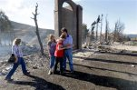 Vern Smith, right, embraces his son Spencer, 13, as daughter Mary, 17, stands with them and his wife, Julie, joins them in front of the remains of their fire-destroyed home Monday, June 29, 2015, in Wenatchee, Wash. The wildfire fueled by high temperatures and strong winds roared into town Sunday afternoon. The blaze ignited in brush just outside Wenatchee, quickly burning out of control. (AP Photo/Elaine Thompson)