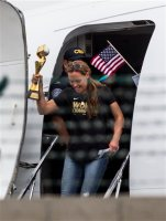 The U.S. women's national soccer team captain Christie Rampone holds the trophy as the team arrives at Los Angeles International Airport, Monday, July 6, 2015. The team defeated Japan 5-2 during Sunday's FIFA Women's World Cup in Vancouver. (AP Photo/Ringo H.W. Chiu)