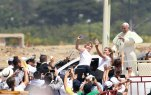 Pope Francis waves to the crowd as he rides in the popemobile through Samanes Park, where he will celebrate Mass, in Guayaquil, Ecuador, Monday, July 6, 2015. A crowd estimated at 1 million people, greeted Francis on the packed dirt of Samanes Park for a late-morning Mass. (AP Photo/Fernando Vergara)