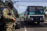 A soldier guards a street as a passenger bus drives past, in San Salvador, El Salvador, Wednesday, July 29, 2015. Bus routes across San Salvador have been disrupted by a series of violent attacks and threats against those who continue to drive their routes. Since Sunday night, nine drivers have been killed, prompting authorities to increase security throughout the city. (AP Photo/Salvador Melendez)
