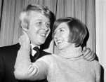 FILE - In this Jan. 4, 1969 file photo, British pop singer Cilla Balck smiles with her fiance Bobby Willis, in Mayfair, London. Police say big-voiced British singer and TV host Cilla Black has died aged 72. Spanish police said Sunday that the singer, who had a home in Estepona, southern Spain, died Saturday, Aug. 1, 2015. Born Priscilla White, Black worked as a teenager in the cloakroom of Liverpool's Cavern Club, where her musical talent was spotted by The Beatles. (AP Photo, File)
