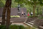 """People walk past a statue of Gen. John J. Pershing, who had served as general of the Armies in World War I, in Pershing Park, at 14th Street and Pennsylvania Avenue NW, in Washington, Wednesday, Aug. 19, 2015. A jury has selected five design concepts for a new national World War I Memorial to be built in the memorial park in Washington, with ideas ranging from neoclassical architecture to a portrait wall of the """"American family."""" Congress has dedicated the existing park along Pennsylvania Avenue near the White House to become a national memorial honoring the veterans of the first world war and the 116,516 American lives lost. A design competition drew 350 entries, and a jury narrowed those to five finalists announced Wednesday. (AP Photo/Carolyn Kaster)"""