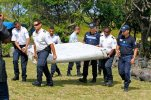 FILE - In this photo dated Wednesday, July 29, 2015, French police officers carry a piece of debris from a plane in Saint-Andre, Reunion Island. Malaysian officials said Sunday, Aug. 2, 2015 that they would seek help from territories near the island where a suspected piece of the missing Malaysia Airlines jet was discovered to try to find more possible debris from the plane. (AP Photo/Lucas Marie, File)