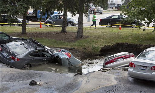Cars are sumberged in a sinkhole at an apartment complex, Friday, Aug. 14, 2015, in Madison, Wis. About 300 residents of the complex were evacuated after a water pipe break created the sinkhole and potential gas leak. (Steve Apps/Wisconsin State Journal via AP) MANDATORY CREDIT