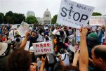 "Protesters hold anti-war placards in front of the National Diet building during a rally in Tokyo, Sunday, Aug. 30, 2015. Thousands of Japanese protested outside the parliament a set of security bills designed to expand the role the country's military. The bills - a cornerstone of Prime Minister's Shinzo Abe's move to shore up Japan's defenses in the face of growing threats in the region - are expected to pass next month despite criticism they undermine Japan's post-war pacifism. A placard at bottom center reads ""No War, No Nuke."" (AP Photo/Shizuo Kambayashi)"