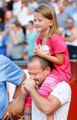 Chad Carlile cries for his son Kaiser as he holds his daughter Keirsie, 7, on his shoulders during a tribute to his son prior to a baseball game between the Liberal Bee Jays and the Seattle Studs at Lawrence-Dumont Stadium in Wichita, Kan., Tuesday, Aug. 4, 2015. Kaiser Carlile was accidentally struck by a bat near the on-deck circle Saturday and died from his injuries Sunday. (Fernando Salazar/The Wichita Eagle via AP) LOCAL TELEVISION OUT; MAGS OUT; LOCAL RADIO OUT; LOCAL INTERNET OUT; MANDATORY CREDIT