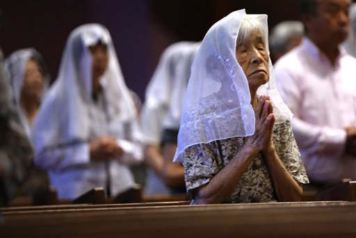 Catholics offer prayers at an early morning mass to pay respect to the victims of the atomic bombing at the Urakami Cathedral in Nagasaki, southern Japan Sunday, Aug. 9, 2015. Seventy years ago, a U.S.-dropped atomic bomb detonated about 500 meters (1,500 feet) from the church, killing two priests who were hearing confessions and about 30 others inside. The more than 70,000 who died in Nagasaki in the Aug. 9, 1945, bombing included 8,500 of the cathedral's 12,000 parishioners, decimating the largest Christian community in Japan. (AP Photo/Eugene Hoshiko)