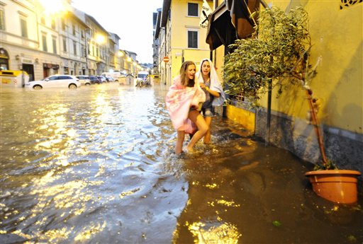 In this picture taken Saturday, Aug. 1, 2015, people make their way on a flooded street in Florence, Italy. A thunderstorm, hail and fierce winds Saturday evening pummeled Florence, flooding basements and knocking down hundreds of trees. (Maurizio Degl'Innocenti/ANSA Via AP)
