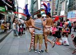In this photo taken on Tuesday, July 28, 2015, a tourist poses for a photo with two women clad in thongs and body paint in Times Square, in New York. New York City Mayor Bill de Blasio is promising to take action against women who pose nearly naked for photos in Times Square in exchange for cash. (AP Photo/Julie Jacobson)