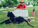 "In this photo provided by Walter Skold, of Freeport, Maine, Skold poses Friday, Aug. 7, 2015, at the grave of his father in York, Pa. The Dead Poets Society of America founder visited his father's grave after completing his tour of 97 poets' graves in 70 days. With Skold is his mascot ""Raven,"" a stuffed black panther that was given to him. (Walter Skold via AP)"