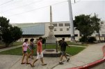 People walk past a monument dedicated to the Battle at Liberty Place in New Orleans, Wednesday, Sept. 2, 2015. Opponents and supporters of a move to remove  prominent Confederate monuments are preparing to speak out over the fate of the monument in the French Quarter, dedicated to a violent uprising against a Reconstruction-era government. The fate of the monument is being discussed by a commission that oversees the French Quarter. (AP Photo/Gerald Herbert)