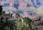 In this Wednesday, Aug. 19, 2015 photo, visitors gather at an outlook on the South Rim of Grand Canyon National Park in northern Arizona. The Grand Canyon and other big national parks are seeing more visitors than usual this year, partly driven by good weather, cheap gas and marketing campaigns. (AP Photo/Felicia Fonseca)