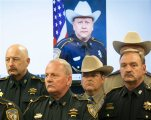 AP10ThingsToSee - Law enforcement officers attend a news conference on the shooting death of Harris County Sheriff's Deputy Darren Goforth, pictured in background, in Houston on Saturday, Aug. 29, 2015. Prosecutors on Saturday charged Shannon J. Miles with capital murder in the Friday killing of Goforth at a suburban Houston gas station. (Marie D. De Jesus/Houston Chronicle via AP) MANDATORY CREDIT