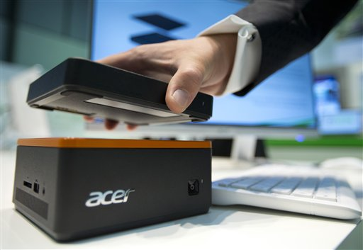 A staff member holds an external hard drive over a Revo Build modular PC at the stand of the electronic company Acer at the IFA 2015 tech fair  in Berlin, Germany, Wednesday, Sept. 2, 2015. (AP Photo/Michael Sohn
