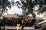 A refugee child looks through a bus window as they leave for Istanbul, abandoning plans to cross to Europe near Turkey's western border with Greece and Bulgaria, in Edirne, Turkey, Wednesday, Sept. 23, 2015. Hundreds of migrants made the trek to Edirne in the hope of being allowed to cross into neighboring Greece or Bulgaria and avoid the often-risky journey across the Aegean Sea. (AP Photo/Emrah Gurel)