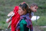 A migrants carries a child as they arrive at the Hungarian-Austrian border in Nickelsdorf, Austria, Saturday, Sept. 5, 2015, where they came from Budapest as Austria in the early-morning hours said it and Germany would let them in. (AP Photo/Frank Augstein)