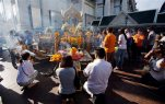 Visitors pray at Phra Phrom, the Thai interpretation of the Hindu god Brahma, at the Erawan Shrine in Bangkok, Thailand, Friday, Sept. 4, 2015. Thai authorities unveiled the restored centerpiece Friday of the Erawan Shrine, in the latest bid to restore confidence among Bangkok's tourism and business communities almost three weeks after a deadly bombing. (AP Photo/Sakchai Lalit)