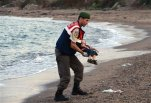 A paramilitary police officer carries the lifeless body of an unidentified migrant child, lifting it from the sea shore, near the Turkish resort of Bodrum, Turkey,  early Wednesday, Sept. 2, 2015.  A number of migrants are known to have died and some are still reported missing, after boats carrying them to the Greek island of Kos capsized. (AP Photo/DHA) TURKEY OUT