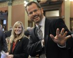 """FILE- In this Jan. 14, 2015 file photo, Rep. Cindy Gamrat, R-Plainwell, and Rep Todd Courser, R-Lapeer wave to reporters in the House of Representatives in Lansing, Mich. An investigation of the Michigan lawmakers who had an extramarital affair alleges numerous instances of deceptive and """"outright dishonest"""" conduct to cover it up. (Dale G. Young /Detroit News via AP)  DETROIT FREE PRESS OUT; HUFFINGTON POST OUT; MANDATORY CREDIT"""
